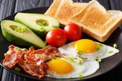 Hartelijk ontbijt: gebraden eieren met bacon, avocado, toost en toma stock afbeeldingen