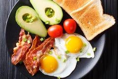 Hartelijk ontbijt: gebraden eieren met bacon, avocado, toost en toma royalty-vrije stock afbeelding