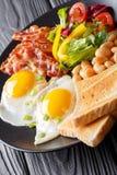 Hartelijk ontbijt: gebraden eieren met bacon, bonen, toost en vers stock afbeeldingen