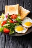 Hartelijk ontbijt: gebraden eieren met verse groentesalade en toas royalty-vrije stock afbeelding