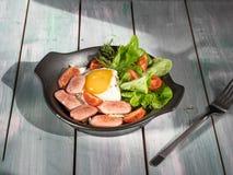 Hartelijk ontbijt van roereieren met worsten, tomaten en bladsla Dien op een houten rustiek dienblad stock foto's