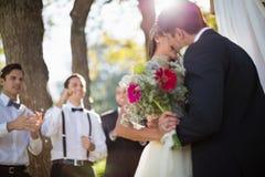 Hartelijk paar die elkaar in park kussen stock afbeeldingen