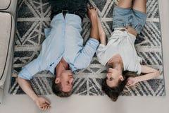 Hartelijk paar die en op het tapijt liggen ontspannen stock afbeeldingen