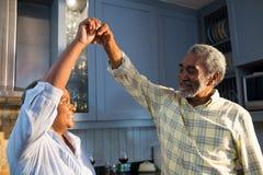 Hartelijk paar die in keuken dansen stock fotografie