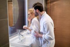 hartelijk paar die spiegel in witte badjassen bekijken stock afbeelding