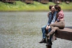 Hartelijk paar die terwijl het zitten op houten pijler kussen royalty-vrije stock foto's
