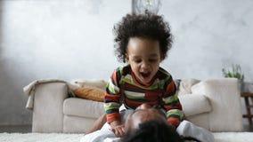 Hartelijke gelukkige papa die zijn krullende zoete zoon kussen stock video