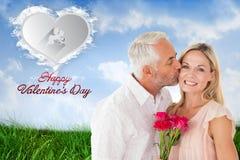 Hartelijke mens die zijn vrouw op de wang met rozen kussen Royalty-vrije Stock Afbeelding