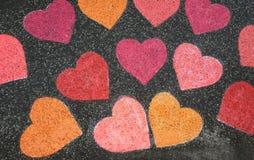 Harten met kleurkrijtje op de straat worden geschilderd die royalty-vrije stock afbeeldingen