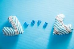 Harten met liefde het van letters voorzien op blauwe achtergrond De dagconcept van de valentijnskaart ` s Stock Foto's