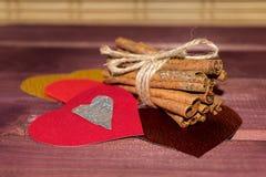 Harten met pijpjes kaneel en trouwring op hout Stock Afbeeldingen