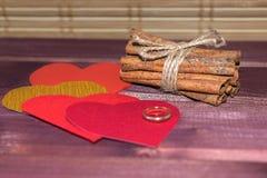 Harten met pijpjes kaneel en trouwring op hout Royalty-vrije Stock Foto