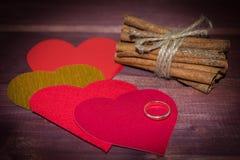 Harten met pijpjes kaneel en trouwring op hout Stock Afbeelding