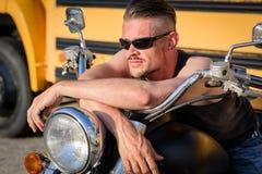 Harter Junge mit Sonnenbrillen räkelnd auf seinem Zerhackermotorrad Stockfoto