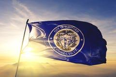 Hartford-Stadthauptstadt von Connecticut des Flaggentextilstoffgewebes Vereinigter Staaten, das auf den Spitzensonnenaufgangnebel lizenzfreie stockfotografie