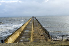 Hartlepool Headland Breakwater. The breakwater in the Headland area of Hartlepool, Cleveland, England, pointing out to sea with the industrial complex on Teeside Stock Photos