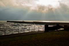 Hartlepool Headland Breakwater. A view of the breakwater off Hartlepool headland area in low light with the sun coming through the clouds Stock Image