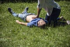 Hartmassage aan een onbewuste kerel na verwonding royalty-vrije stock afbeelding