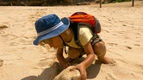 Hartnäckiger Stoß des kleinen Jungen ein großer Stein auf einem Strand mit großem Wellen Melasti-Strand auf der Bali-Insel, Indon stock footage