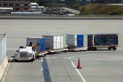 Hartsfield-Jackson Airport ground crew. Atlanta, Georgia, USA - October 13, 2016: Dolly fleet operator drives vehicle, which pulls dollies for baggage unit load Royalty Free Stock Photography