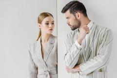 hartstochtelijke jonge mannelijke en vrouwelijke modellen in uitstekende jasjes die elkaar bekijken stock fotografie