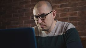Hartstochtelijke mens met glazen die met laptop in het bureau werken Een mannelijke schrijver typt tekst op laptop toetsenbord, c stock footage