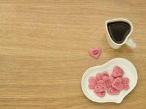 Hartvorm van kop met koffie en hartvorm van plaat met roze liefjes in witte plaat De kop van de koffie met hart Hoogste mening Ge Stock Foto