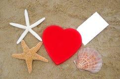 Hartvorm, zeesterren, zeeschelp en document op het strand Stock Afbeeldingen