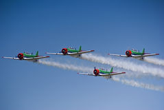 Harvard Aerobatic Team - Low Level Flyby. Harvard aerobatic team, in a display of four up formation flying, with smoke trails Royalty Free Stock Photos