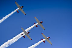 Harvard Aerobatic Team, Smoke On, Flyover. Harvard aerobatic team, in a display of four up formation flying, with smoke trails. View from directly below, looking royalty free stock image