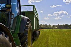 Harvest. A farm tractor with trailer parked on a field royalty free stock photos