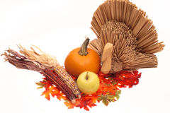 Harvest!. A turkey with Indian Corn, a pumpkin and a yellow apple sit amonst colorfu autumn leaves.  Isoloated on a white background Royalty Free Stock Images