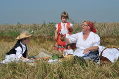 Harvest and breakfast. Traditional breakfast in a field at the time of harvest. Hungarian folk costume Stock Image