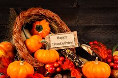 Harvest cornucopia with Happy Thanksgiving gift tag. Harvest cornucopia close up with Happy Thanksgiving gift tag on dark wood background Royalty Free Stock Photo