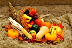 Harvest cornucopia. Harvest or Thanksgiving cornucopia filled with vegetables on a burlap and wood background Royalty Free Stock Photos