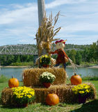 Harvest display with pumpkins, hay bales and happy scarecrow Royalty Free Stock Photos