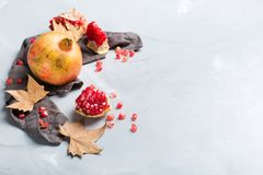 Harvest fall autumn concept. Ripe juicy pomegranate. Autumn fall harvest concept. Ripe juicy pomegranate on a cozy kitchen table. Copy space background royalty free stock image
