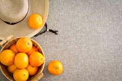 Harvest of farm fresh oranges with a straw sunhat Royalty Free Stock Photo