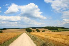Harvest Fields and Road. Under cloudy skies in high summer Stock Photos