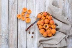 Harvest of fresh apricots in a wicker basket. And apricot pieces with a knife on vintage wooden table stock photography