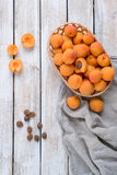 Harvest of fresh apricots in a wicker basket. Pieces of apricot and apricot seeds on a light wooden background stock images