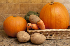 Harvest of fresh fall or autumn vegetables. In a shallow wicker basket on a granite counter including carrots, potatoes, broccoli and pumpkins Stock Photo