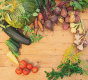 Harvest of fresh vegetables on wooden background. Top view. Potatoes, carrot, squash, peas, tomatoes Stock Photo