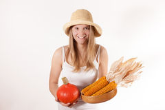 Harvest girl with hat is holding pumpkin and corn Stock Photo