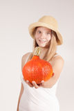 Harvest girl with hat is offering pumpkin Royalty Free Stock Photos