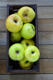 Harvest of green apples in wooden crate Stock Photo