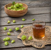 Harvest of hops and a glass cup with a drink from the hops Royalty Free Stock Photo