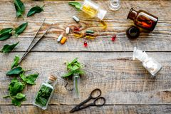 Harvest medicinal herb. Leaves, bottles and sciccors on wooden background top view Royalty Free Stock Photos