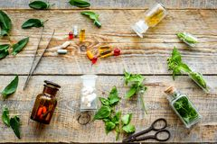 Harvest medicinal herb. Leaves, bottles and sciccors on wooden background top view Stock Photography