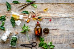 Harvest medicinal herb. Leaves, bottles and sciccors on wooden background top view copyspace Stock Image